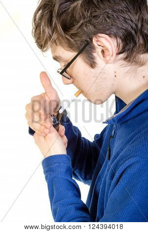 Teenage boy lighting a cigarette with a lighter