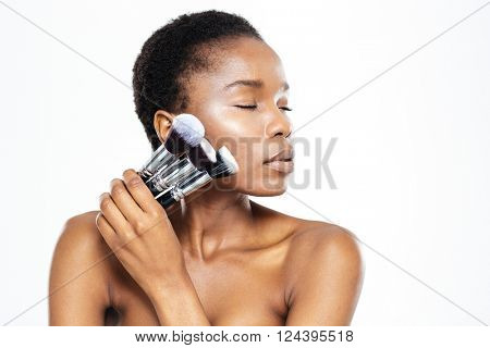Relaxed afro american woman with closed eyes holding makeup brushes isolated on a white background