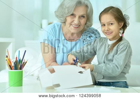 Portrait of a happy grandmother with granddaughter cutting together