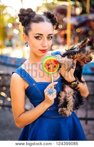 Bright makeup beautiful girl with Yorkshire Terrier holding watermelon lollipop near carousel in a park.