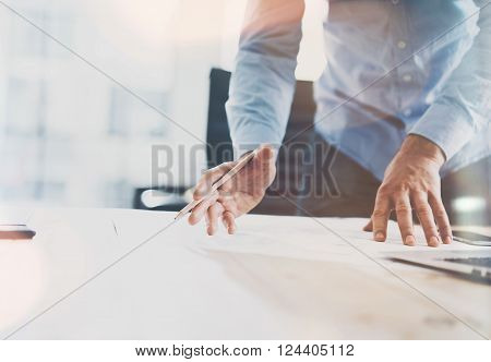 Working process startup. Businessman working at the wood table with new finance project. Generic design notebook on table. Pencil holding hand. Horizontal mockup.