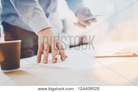 Photo work process banker.Man working wood table with new  business project.Modern laptop table.Pencil holding hand, typing  contemporary smartphone.
