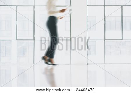 Photo business woman in motion, wearing modern suit. Open space loft office. Holding papers hands. Analyze plans, meeting, panoramic windows background. Motion blur.