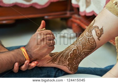 Bride gets peacock Mehandi tattoo on her leg by Mehndi artist ** Note: Visible grain at 100%, best at smaller sizes