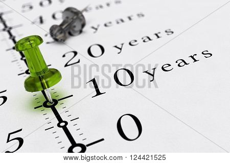 10 years written on a paper with a blue pushpin concept image for business vision or long term prospective. 3D illustration