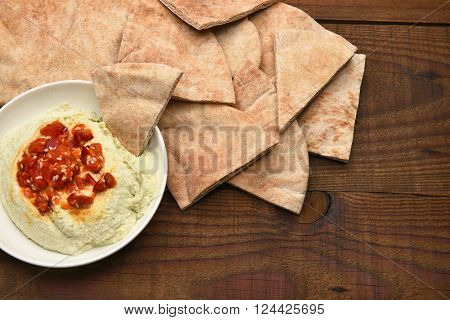 Pita bread wedges and edamame hummus on a rustic wooden table. Horizontal format from a high angle.