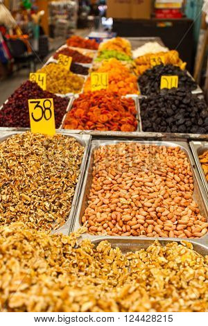 Close-up of different nuts and dried fruits in metal boxes. The counter on the Mahane Yehuda Market in Jerusalem, Israel.