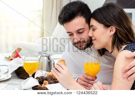 Close up portrait of young honeymoon couple enjoying room service in hotel suite.