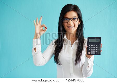 Young Business Woman Show Calculator And Gesture Ok