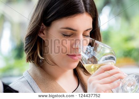 Close up portrait of attractive young woman searching for aroma in white wine at tasting.