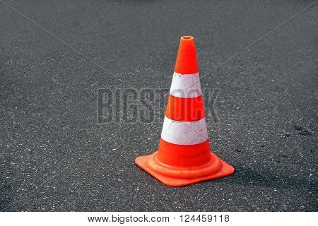 traffic cone, with white and orange stripes on gray asphalt, copy space