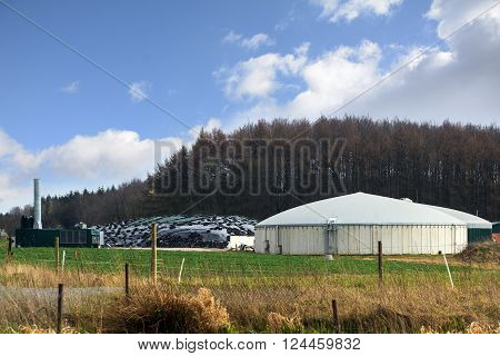 biogas plant for renewable energies between field and forest with bare trees blue sky with clouds