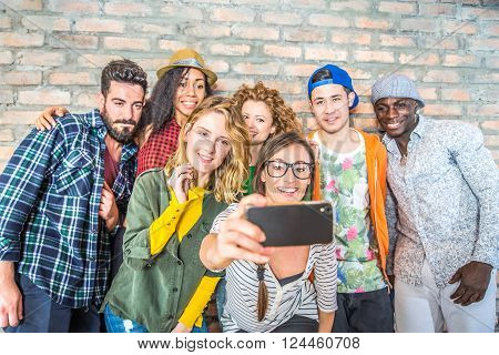Group of people with coloroful trendy clothes bonding together and having fun - Young cheerful friends taking a selfie