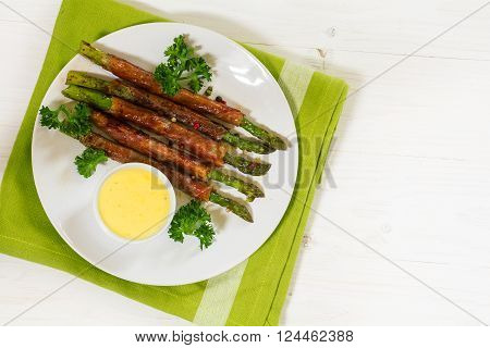 grilled green asparagus wrapped in prosciutto bacon with parsley garnish and hollandaise sauce, white plate, green napkin on a white painted wooden background, lage copy space, view from above