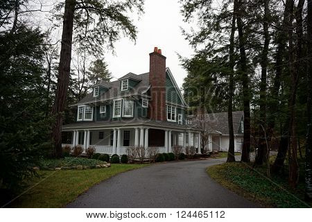 HARBOR SPRINGS, MICHIGAN / UNITED STATES - DECEMBER 23, 2015: A large white and green mansion in the private Glenn Woods Association in Harbor Springs, Michigan.