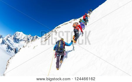 CHAMONIX, FRANCE - MARCH 19, 2016: a group of mountaineer climb a snowy peak. In background the glaciers and the summit of Mont Blanc, the highest european mountain. Chamonix, France, Europe.