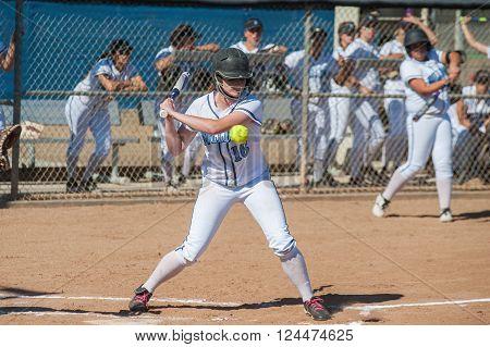 High school softball player taking the high pitch.