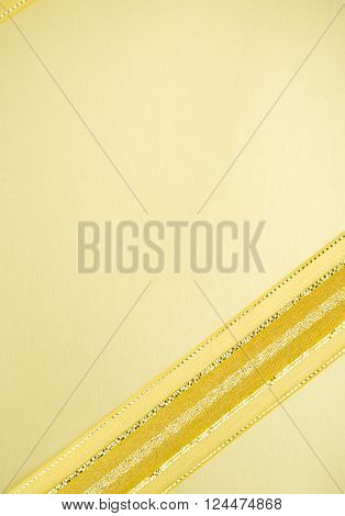 Golden ribbon on yellow able to use for rewarding or greeting card background