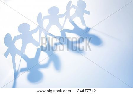 Team of paper doll people casting shadows. Blue tone.