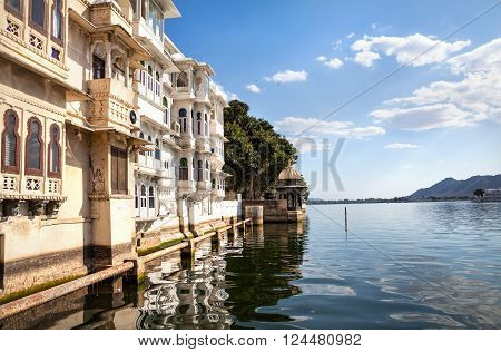 Lake Pichola with residential houses at cloudy sky in Udaipur Rajasthan India