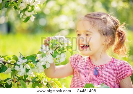 Happy little girl playing in spring apple tree garden