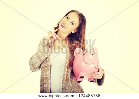 Casual woman holding piggy-bank.