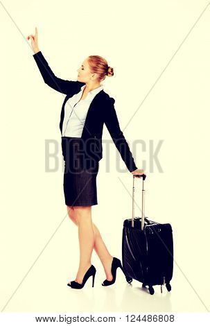 Business woman carrying a suitcase and looking up