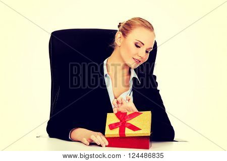 Smile business woman opens a gift box behind the desk