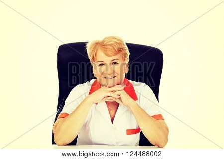 Smile elderly female doctor or nurse sitting behind the desk leaning on hands