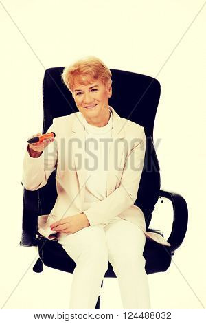 Smile elderly business woman sitting on armchair and holding huge pen