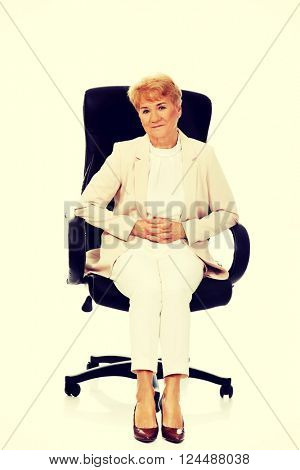 Smile elderly business woman sitting on armchair