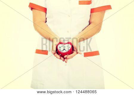Elderly female doctor or nurse holds alarm clock
