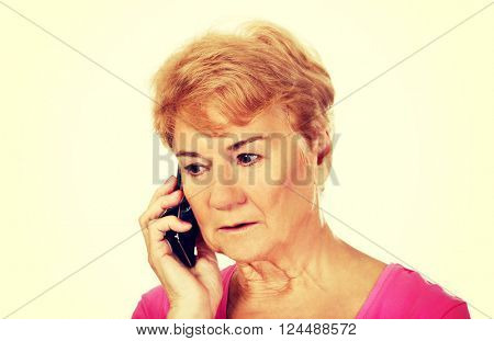 Worried senior woman talking through phone