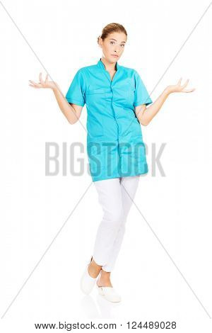 Young female doctor or nurse shrugs