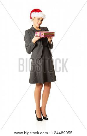 Woman weating Santa hat and holding a present