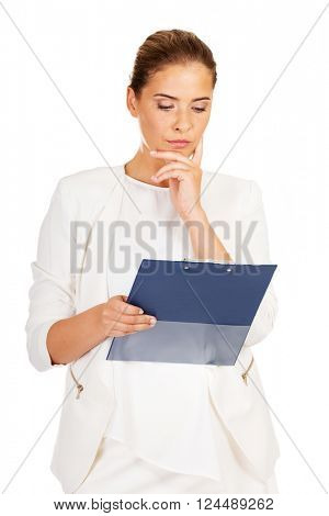 Thoughtful focused businesswoman reading her notes