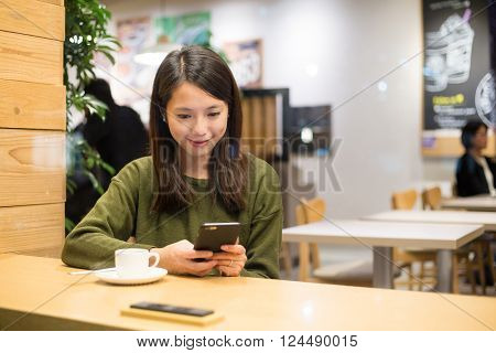 Woman using mobile phone inside coffee at night