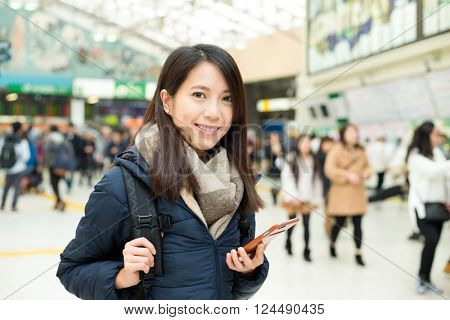 Woman holding cellphone inside train station