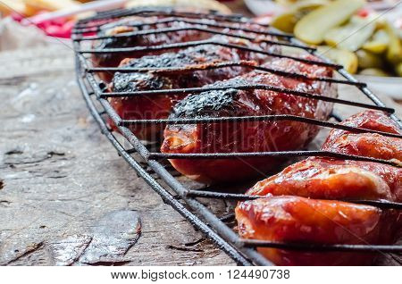 Grilled sausages on wooden table. Grilling sausages in a lattice on wooden background. BBQ with fiery sausages on the grill. Grilling sausages on barbecue grill. Horizontal. Selective focus.