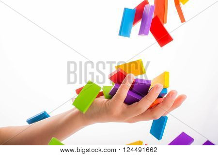 Falling colorful domino off air onto a hand