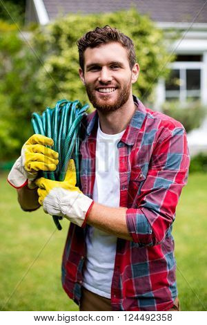 Portrait of smiling man carrying garden hose in yard