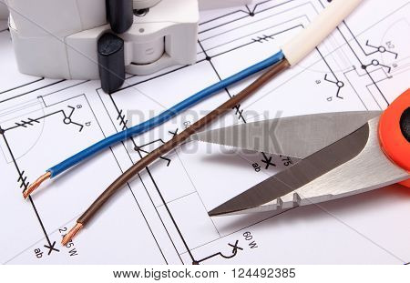 Cable cutter electric wire and fuse lying on construction drawing of house accessories for engineer jobs