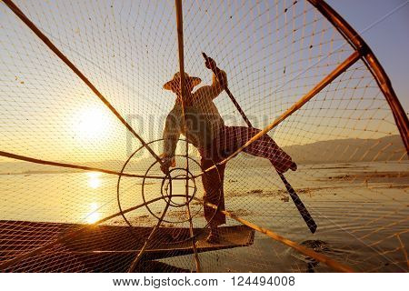 Myanmar travel attraction landmark - Traditional Burmese fisherman with fishing net at Inle lake in Myanmar famous for their distinctive one legged rowing style