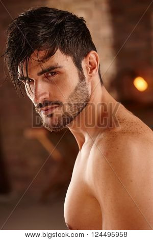 Portrait of handsome charming man with bare chest.