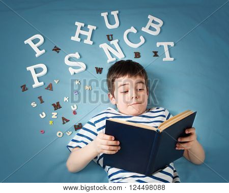 seven years old child lying with book and letters on blue background