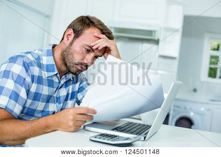 Tensed man looking in documents while sitting by laptop at table in kitchen
