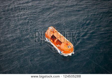 st .Barts , France - November 19, 2015: Orange cruise ship life boat sailing next to st .Barts on dark water