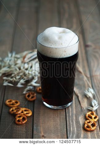 Dark beer with pretzels on wooden table selective focus