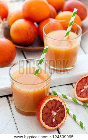 Fresh red oranges juice with fruits on white wooden background selective focus