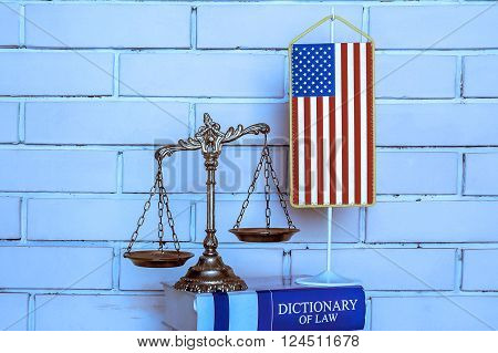 Scales of Justice american flag dictionary of law on the brick wall background BLUE TONE